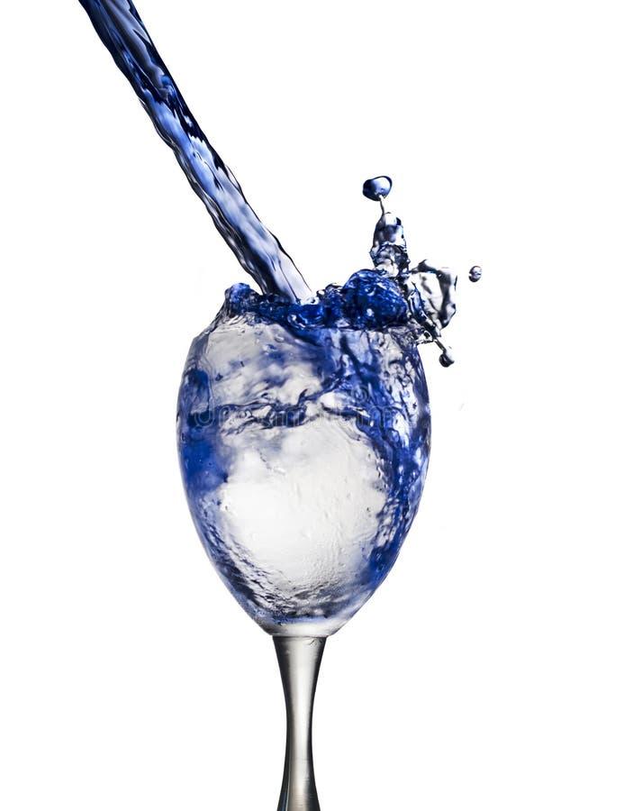 Een blauwe die drank wordt gegoten in wijnglas veroorzakend een plons, op witte achtergrond wordt geïsoleerd stock afbeeldingen