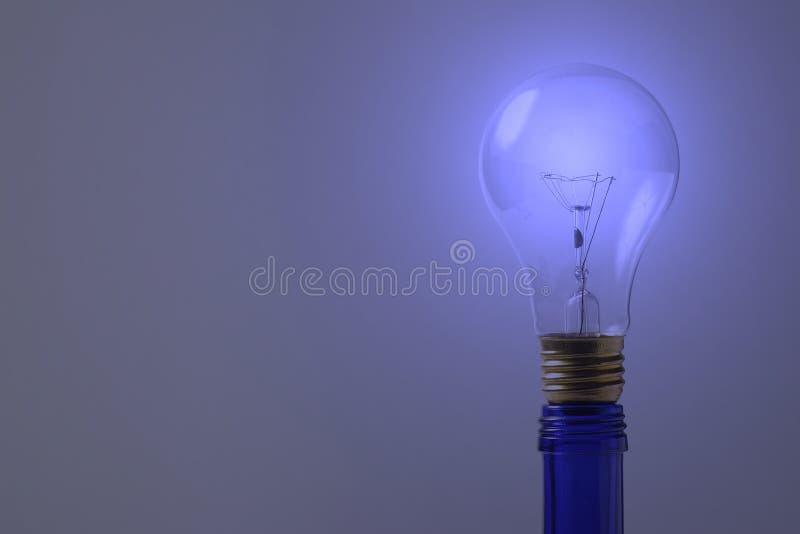 Een blauwe gloeilamp op blauwe fles royalty-vrije stock foto