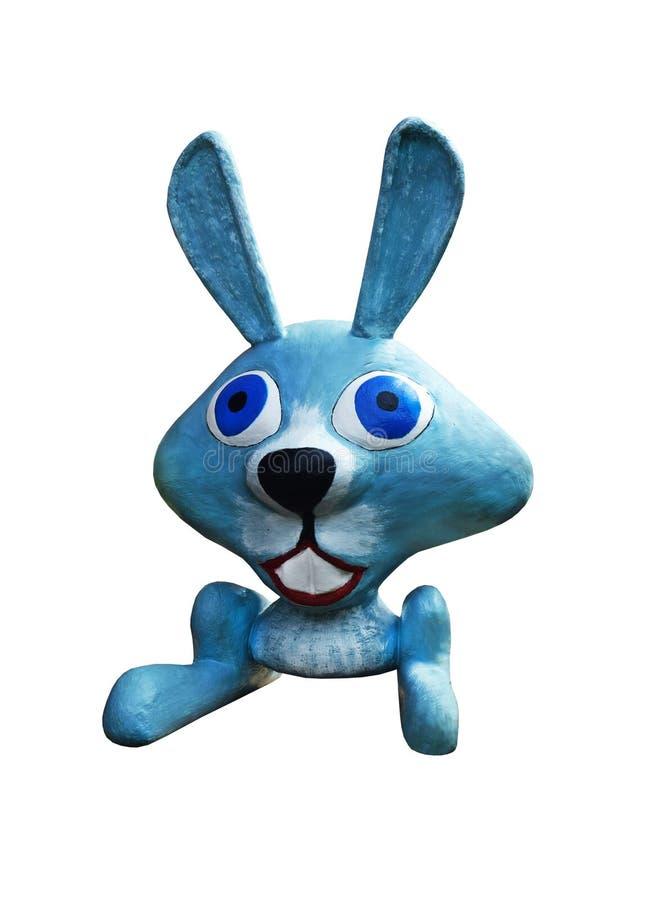 Een blauwe, grappige haas die van klei wordt gemaakt zit het glimlachen met zijn oren, op een witte achtergrond die omhoog worden stock fotografie