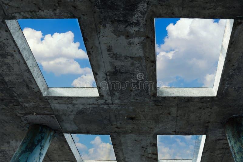 Een blauwe hemel met witte wolken kan door de vensters in een concreet gebouw worden gezien Het concept geloof, vrijheid en hoop royalty-vrije stock foto's