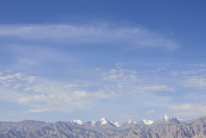 Een blauwe hemel met witte wolken over de woestijnbergen met sneeuwpieken Dag in de bergen royalty-vrije stock foto