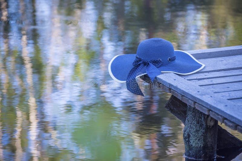 Een blauwe hoed op een houten brug op het meer royalty-vrije stock afbeeldingen