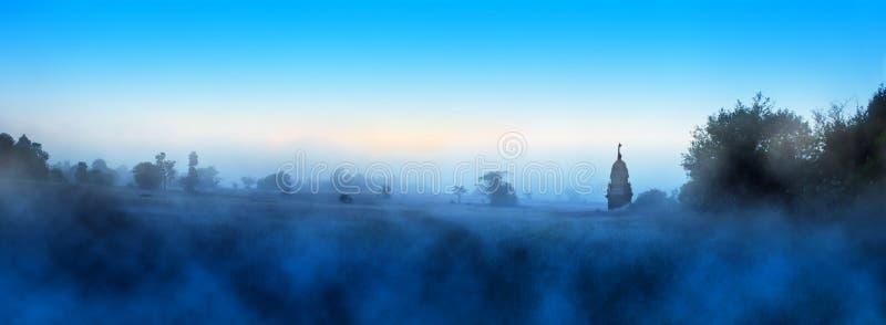 Een blauwe mistige ochtend op weide stock afbeeldingen