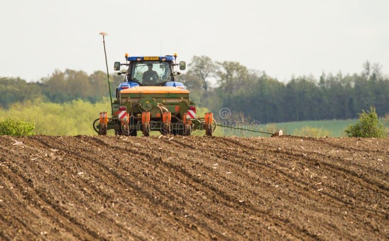 Een blauwe tractor met een zaadboor op een geploegd gebied stock afbeeldingen