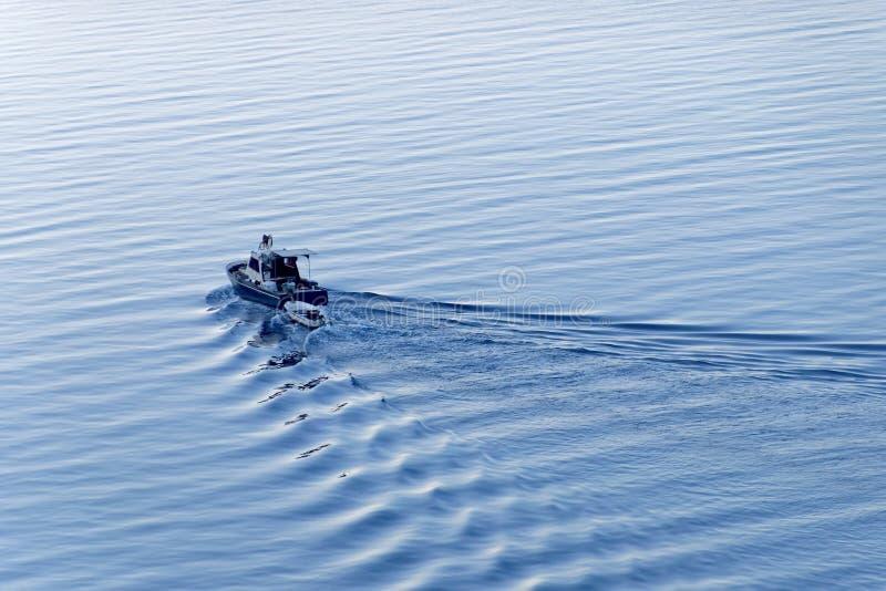 Een blauwe vissersboot die uit op het overzees reizen stock foto's