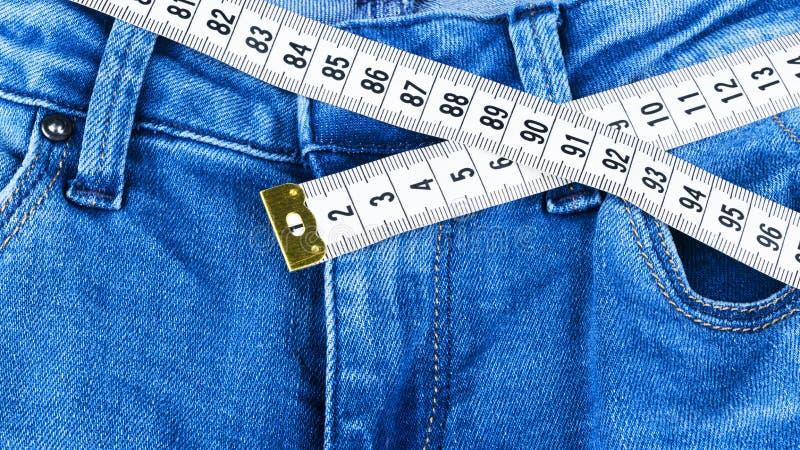 Een blauwe vrouwenjeans en heerser, concept dieet en gewichtsverlies Jeans met het meten van band Gezonde levensstijl, het op die stock fotografie