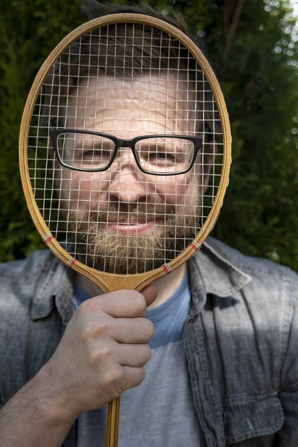 Een blije, grappige mens zette glazen op een badmintonracket en leunde tegen zijn gezicht voor een grap royalty-vrije stock foto's
