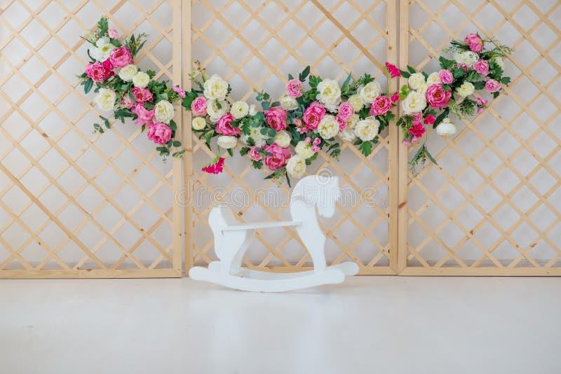 Een bloemkroon die zich dichtbij de houten paardtuimelschakelaar bevinden stock afbeeldingen