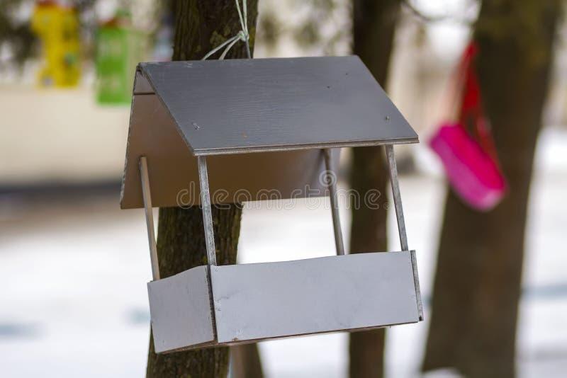 Een blokhuis voor vogels op de boom in de bosplaats aan voer en om voedsel in de wintertijd voor vogels te vinden Vogelvoeder in  stock afbeeldingen