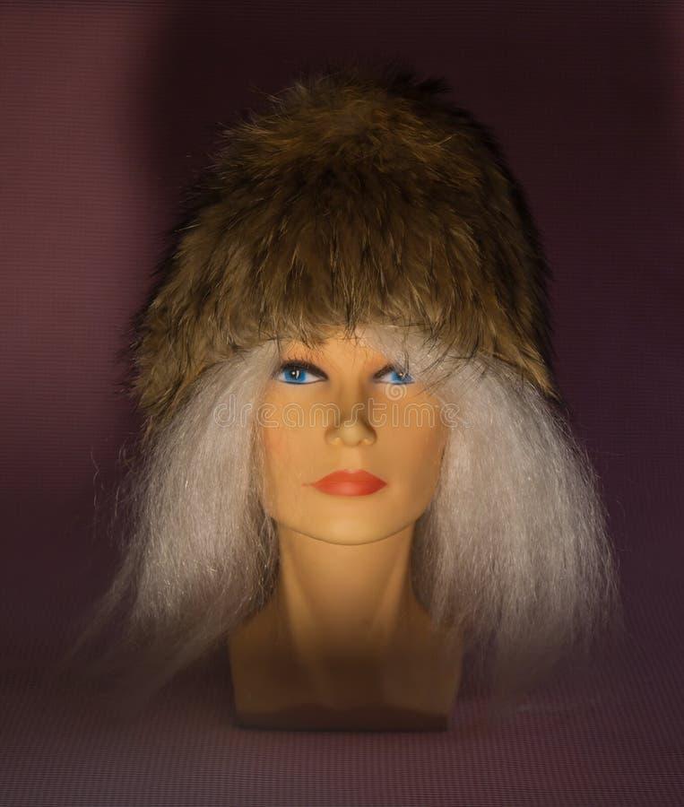 Een blond meisje, met blauwe ogen, in een de winterhoed stock fotografie