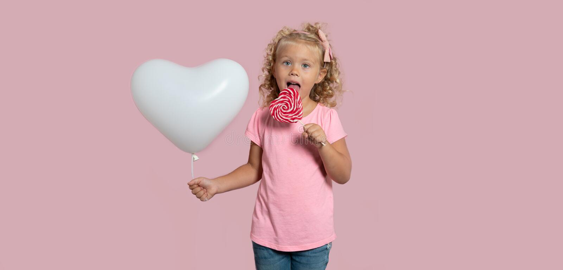 Een blond meisje met wit die baloon en suikergoed, over wit wordt geïsoleerd stock foto's