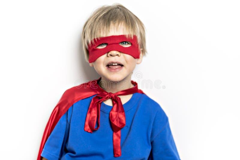 Een blonde Jongenssuperhero in een rode die mantel op witte achtergrond wordt geïsoleerd stock foto's