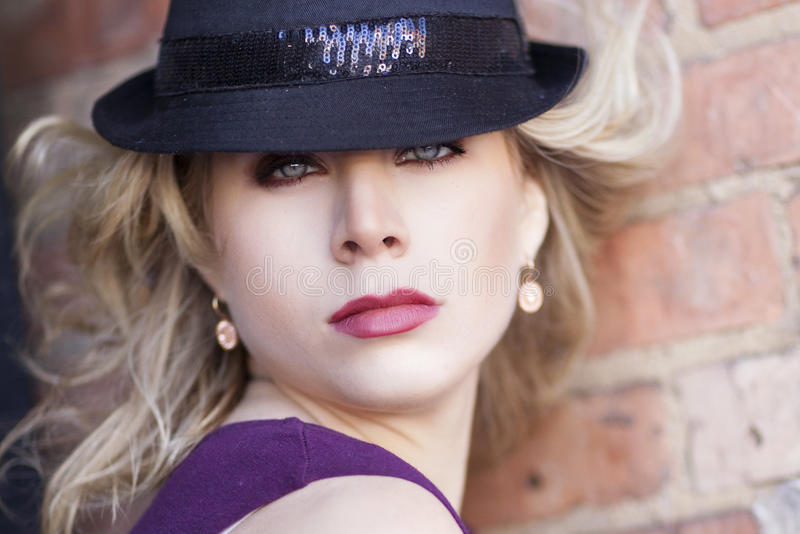 Een blonde krullende haired blauwe eyed vrouw met zwarte sparkly hoed met purpere blouse stock fotografie