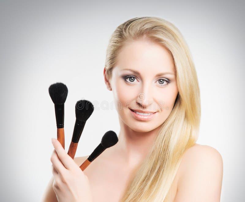 Een blonde make-upborstels van de vrouwenholding royalty-vrije stock fotografie