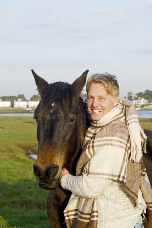 Een blonde mens met zijn bruin paard. stock foto