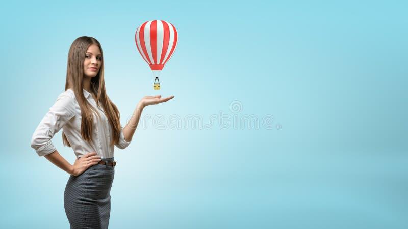 Een blonde onderneemster staat en houdt één handpalm met kleine rode en witte hete luchtballon boven op het stock foto