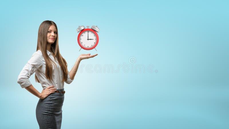 Een blonde onderneemster staat en houdt één handpalm met rode retro wekker op die boven het hangen stock fotografie