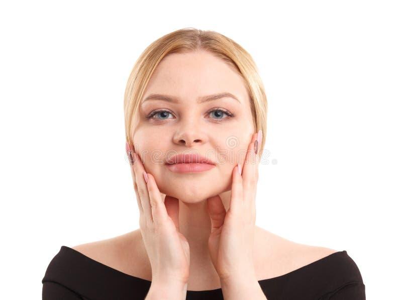 Een blonde vrouw houdt handen dichtbij gezicht Geïsoleerdj op witte achtergrond stock foto