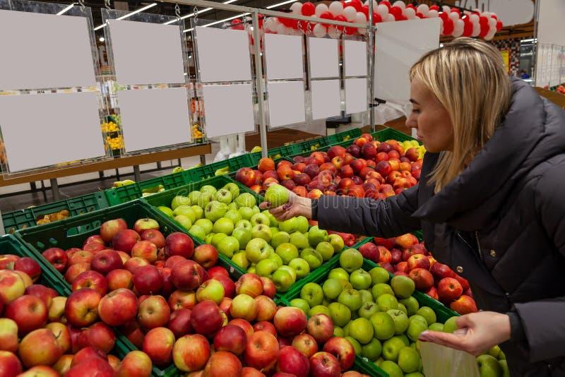 Een blonde vrouw in een supermarkt koopt appelen, leunt door verschilt stock foto's