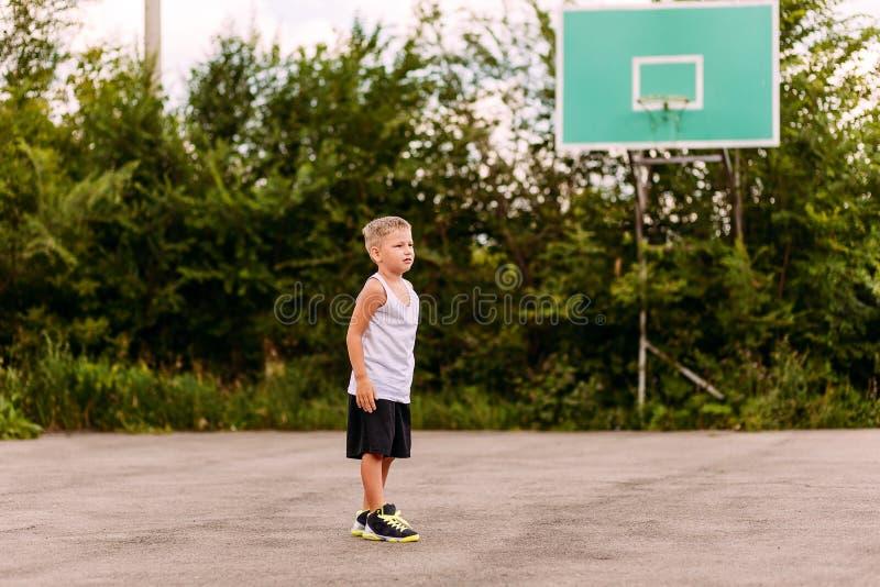 Een blonde zeven-jaar-oude jongen in basketbal eenvormige tribunes op een openluchtbasketbalhof in de zomer Kinderen en sporten, stock afbeeldingen