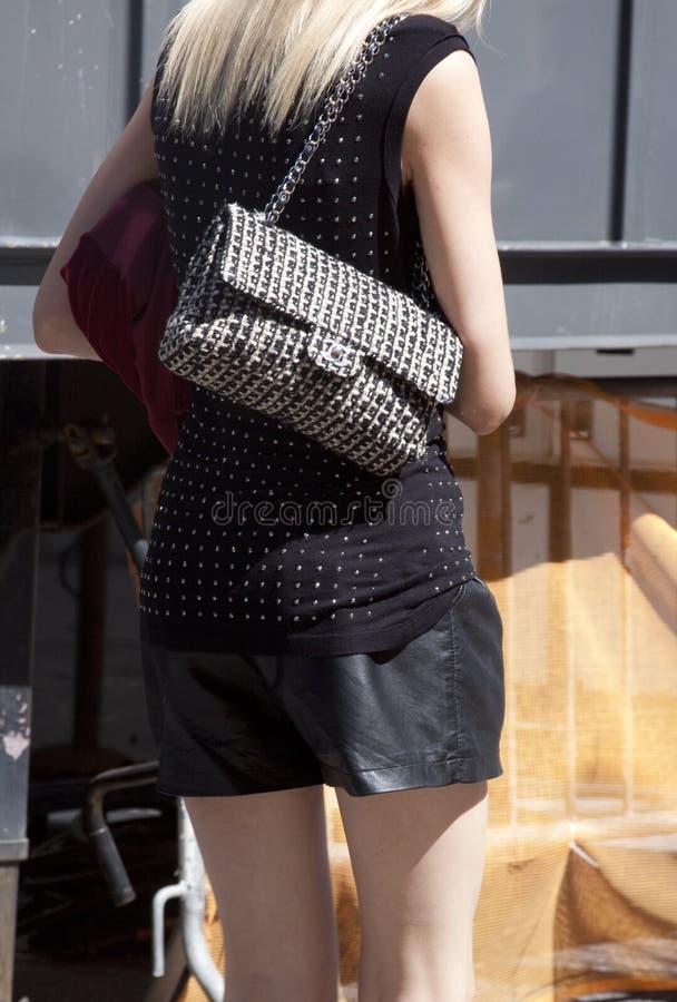 Een blondemannequin met de beurs en het dragen van van Chanel zwarte borrels royalty-vrije stock foto's