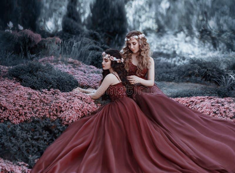 Een blondemeisje die haar donkerbruin meisje` s haar strijken De meisjes zoals zusters zijn gekleed in gelijkaardige marsalakledi royalty-vrije stock afbeelding