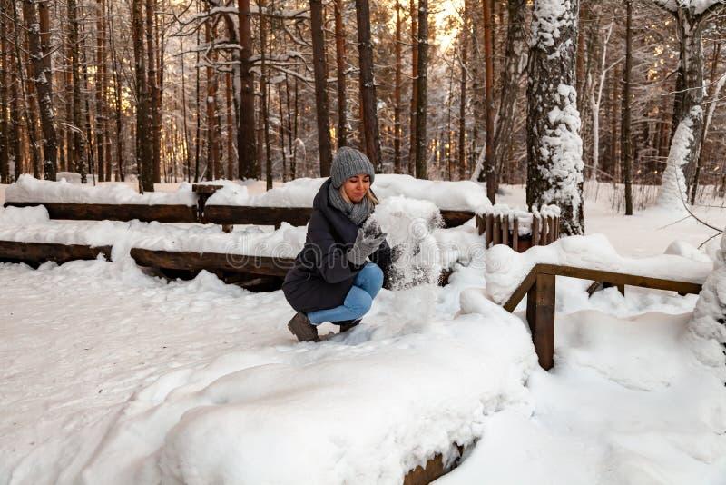 Een blondemeisje in een grijze hoed en een donkerblauw jasje in de winter in het bos hurkt en werpt haar handen tot de sneeuw, he stock foto