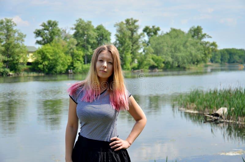 Een blondevrouw in een landschap stock afbeelding
