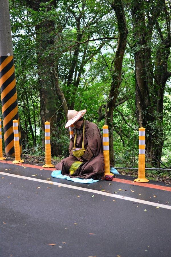 Een Boeddhistische monnikszitting bij de straat in de wildernis van Taiwan stock fotografie