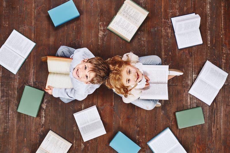 Een boek is als een tuin, die in de zak wordt gedragen Kinderen die dichtbij boeken zitten, terwijl het bekijken camera en het gl stock foto's