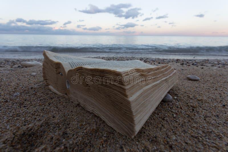 Een boek en geleefd in een verlaten strand op de achtergrond een strand stock foto