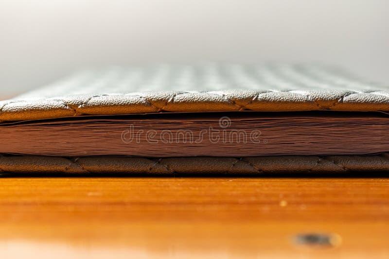 Een boek, een notitieboekje met een geruit patroon op een houten lijst in verschillend stelt De dekking is grijs en zacht met tex royalty-vrije stock foto's