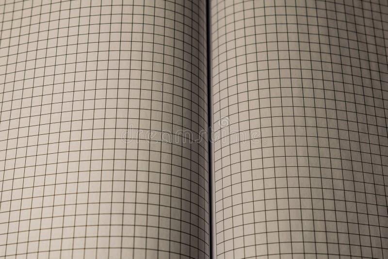 Een boek, een notitieboekje met een geruit patroon op een houten lijst in verschillend stelt De dekking is grijs en zacht met tex stock foto's