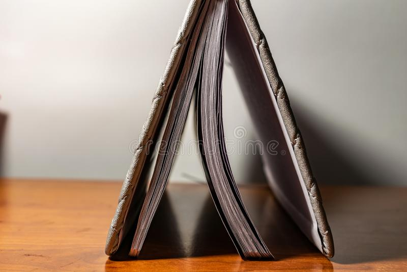 Een boek, een notitieboekje met een geruit patroon op een houten lijst in verschillend stelt De dekking is grijs en zacht met tex royalty-vrije stock foto