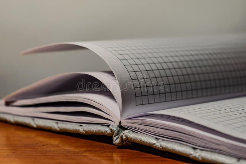 Een boek, een notitieboekje met een geruit patroon op een houten lijst in verschillend stelt De dekking is grijs en zacht met tex stock afbeelding