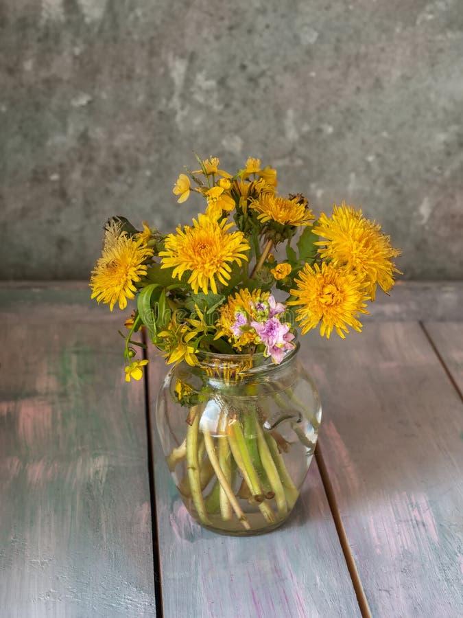 Een boeket van bloeiende paardebloemen en een kleine hyancite in een glaskruik die op een houten lijst, schot bij dichte waaier z stock foto