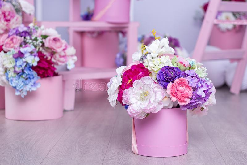 Een boeket van bloemen in een mand op de achtergrond van bloemenregelingen in de studio Mooie Decoratie royalty-vrije stock foto's