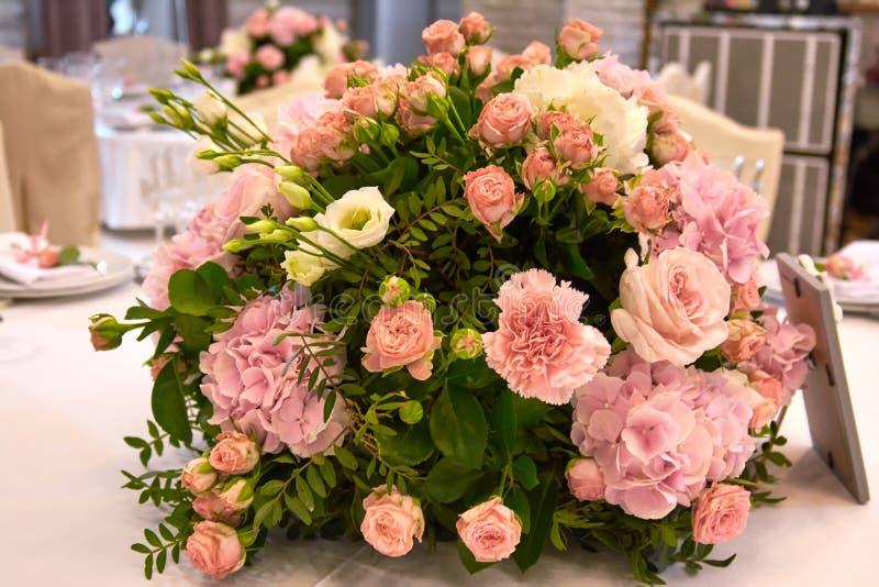 Een boeket van bloemen op een lijst in het restaurant stock foto
