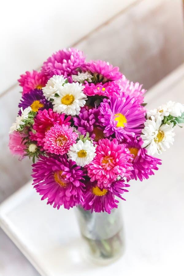 Een boeket van heldere kleurrijke bloemenasters op een lichte achtergrond royalty-vrije stock afbeeldingen