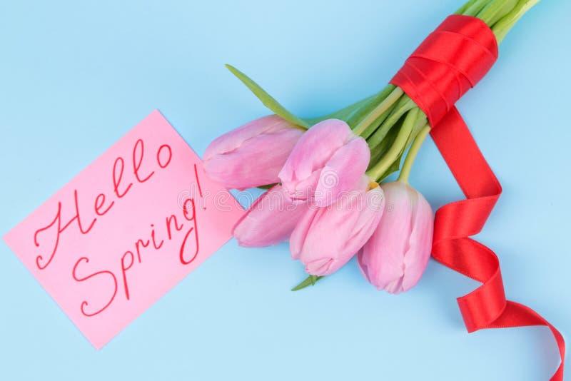 Een boeket van mooie roze bloemen van tulpen op een in heldere blauwe achtergrond De lente vakantie De tekst hello lente Hoogste  stock afbeelding