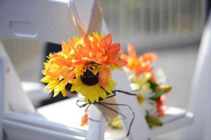 Een boeket van oranje en gouden bloemen is gebonden aan een witte stoel in de zon royalty-vrije stock fotografie