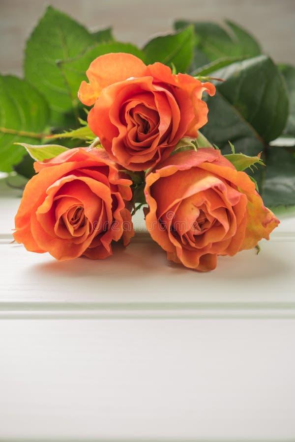 Een boeket van oranje rozen op houten lijst De ruimte van het exemplaar stock fotografie