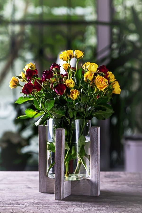 Een boeket van rode en gele rozen op een lijst in een vaas royalty-vrije stock foto's