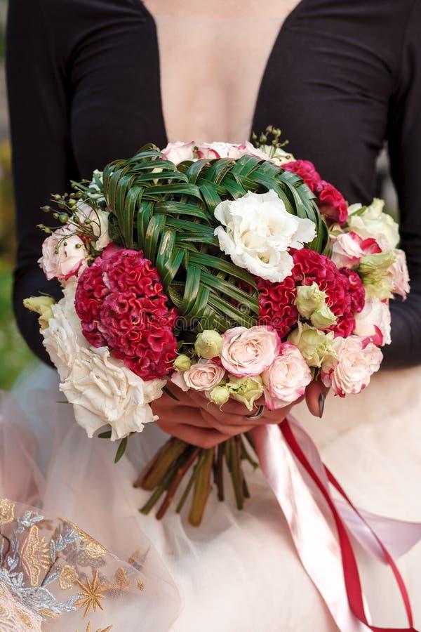 Een boeket van rozen, nevelreflex, celosia, eustoma, robellini, palm stock foto