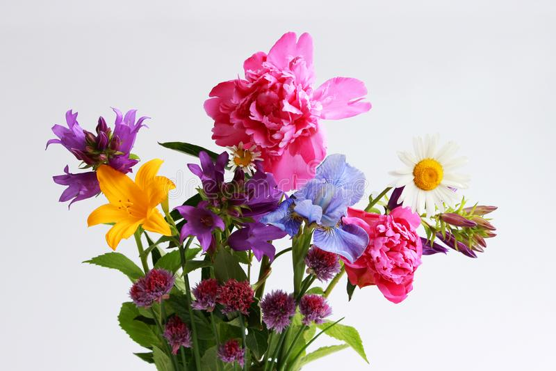 een boeket van verschillende wilde gebied en tuinbloemen: kamille, klok, lelie, bieslook, iris, pioen stock foto's