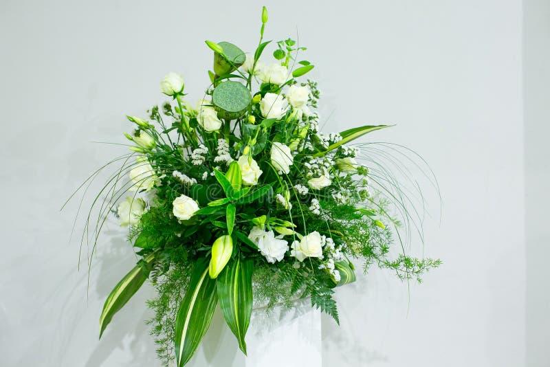 Een boeket van witte rozen, gele gele narcissen, groen en lotuses bevindt zich in een vaas op een marmeren tribune stock afbeeldingen
