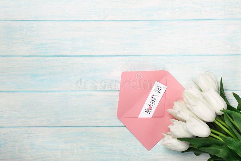 Een boeket van witte tulpen met een van de liefdenota en kleur envelop op blauwe houten raad De dag van de moeder `s royalty-vrije stock fotografie