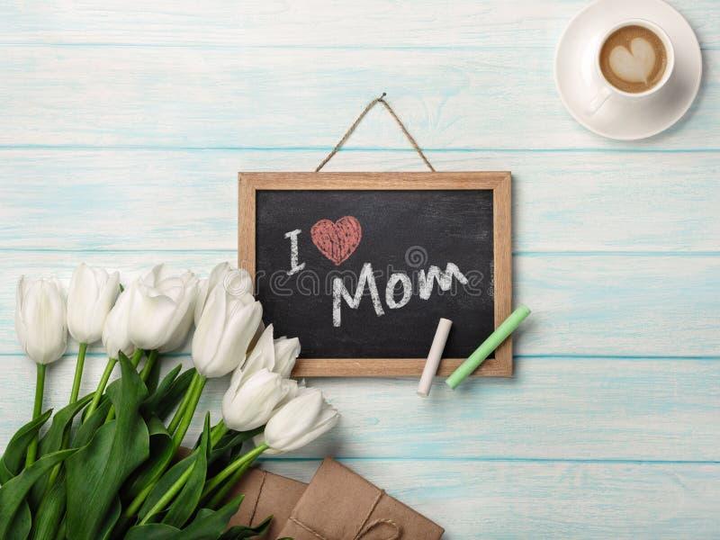 Een boeket van witte tulpen met schoolbord, kop van koffie, liefdenota en enveloppen op blauwe houten raad De dag van de moeder ` royalty-vrije stock afbeeldingen