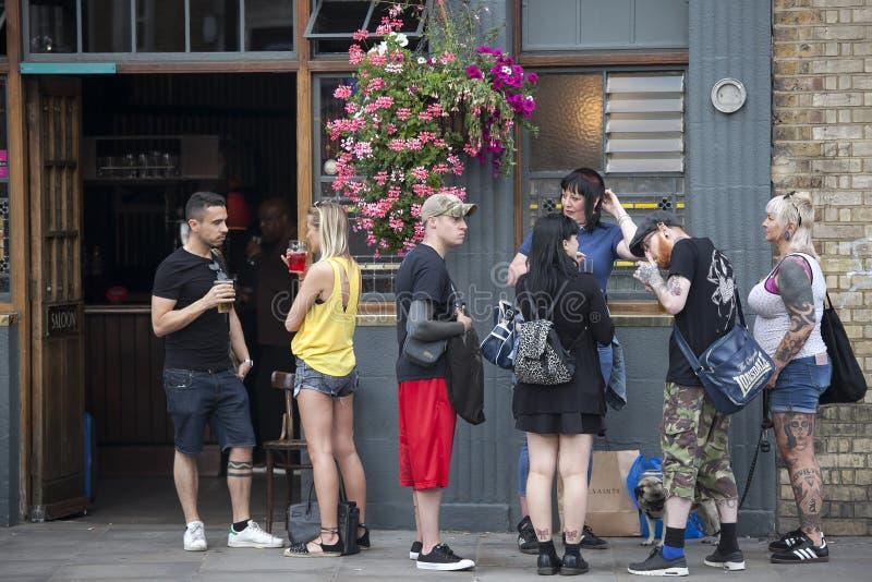een bont menigte van Oost-Londen die een bier buiten bar drinken royalty-vrije stock afbeeldingen