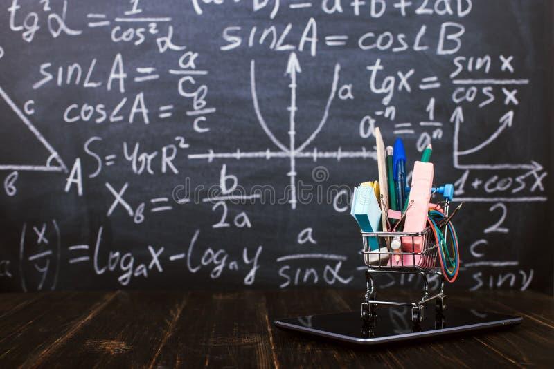 Een boodschappenwagentje met schoollevering op tablet, op lijst tegen achtergrondbord Concept terug naar schoolvoorbereiding en royalty-vrije stock fotografie
